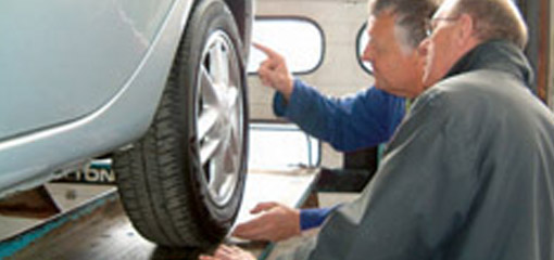 MOT testers looking at a wheel