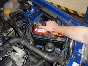 A garage mechanic looking under a car bonnet