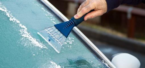 ice scraper being used on frozen windscreen