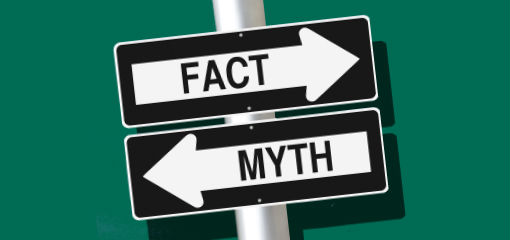 signs pointing in opposite directions. One says 'fact', the other says 'myth'