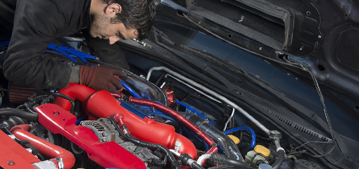 Mechanic looking under bonnet of modified car