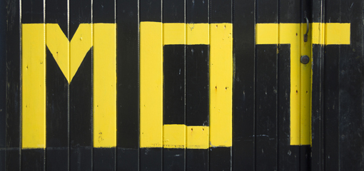 MOT crudely painted in yellow on black wooden background