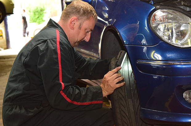 MOT tester checking car tyre