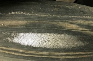 A close up photo of a tyre worn through to the cords.