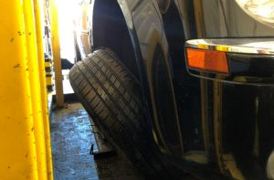 A photo of a car where the wheel is leaning away from the vehicle, indicating it's partially detached.