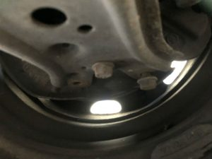 A photo of a vehicle's suspension with lots of bolts missing.