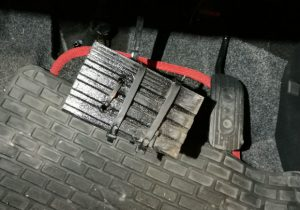 A brake pedal with a section of wooden decking affixed to it with black cable ties.
