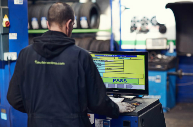 An MOT tester looking at a screen showing an MOT pass.