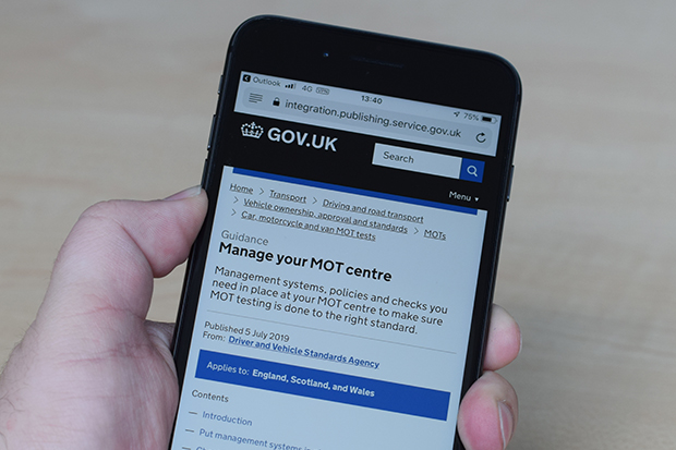Photo of the 'Manage your MOT centre' guide displayed on a mobile phone