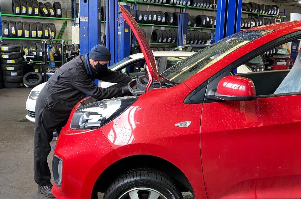 MOT tester inspecting under car