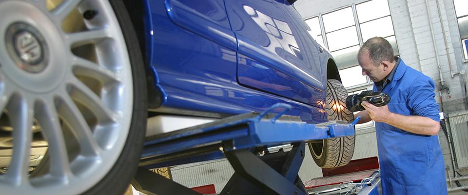MOT tester inspecting blue car